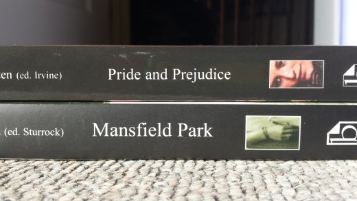 "Image of the spines of ""Pride and Prejudice"" and ""Mansfield Park"" stacked on top of each other on a carpeted floor."