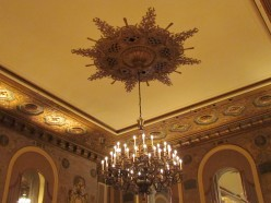 "One of the decadent chandeliers with fantastic craftsmanship and ""graffito,"" etched into the walls. The ballroom ""showcases 20 medallions of history's most acclaimed women, including Cleopatra, Helen of Troy, Pocahontas, and Madame du Barry."""