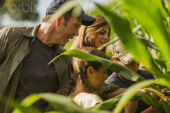 This farm family is examining a corn crop that will soon be harvested.