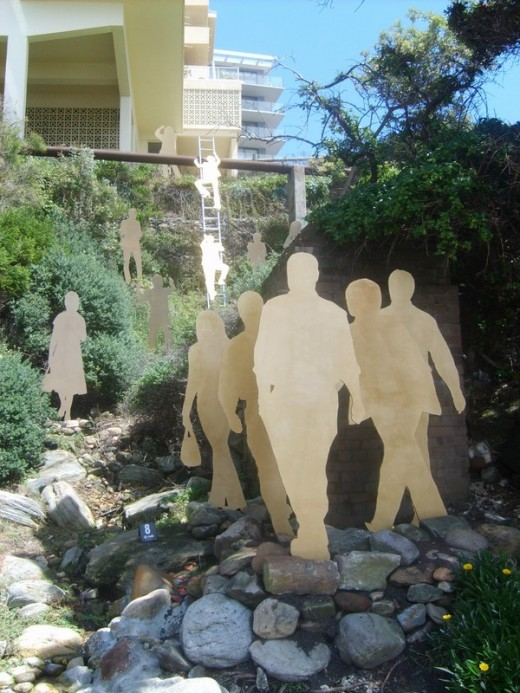 Materials: mdf, gold paint, angle iron, extension ladder, stell. Made by Jan Shaw. Golden silhouttes of stereotypical Sydneyites clamouring and scrambling up slippery slopes in a ract to obtain the pinnacle of possessions, money, power and real estat