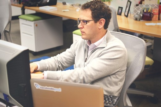 A man staring at his computer while sitting down.