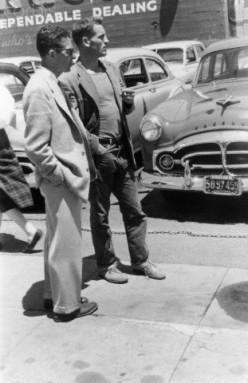 This photo was taken in circa 1955 of Neal Cassady  looking at used cars.
