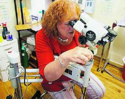Diane Zalecki of Royal Oak's nurse-examiner program uses a special camera to accurately measure injuries of an assault victim. (HUGH GRANNUM/Detroit Free Press)