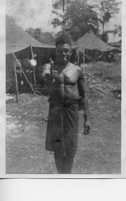 New Guinea native smoking cigarette while visiting U.S. Army camp in WW II