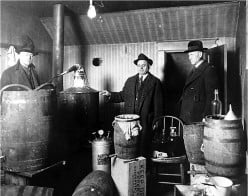 Revenuers inspect a cache of illegal whiskey captured in a recent raid
