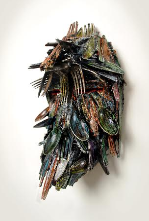 """African Mask""; Plastic forks, spoons, knives and paint; 12.5in x 9in x 9in."