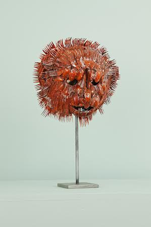 """Lion Head""; Plastic forks, spoons, knives, paint and mirror; 21in x 11in x 8in."