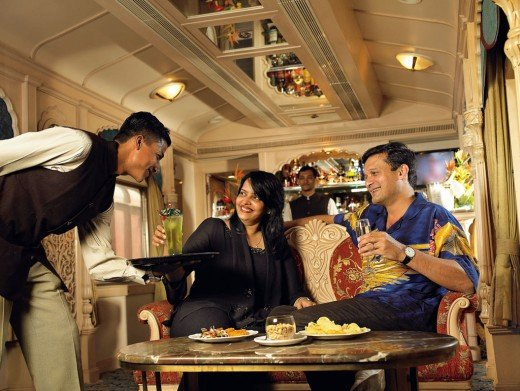 Guest enjoying snacks and drink inside the bar car of the Golden Chariot