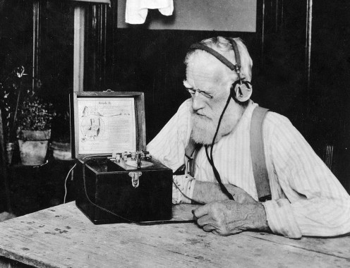 An old farmer - who probably lived through the American Civil War! - listens to one of America's first commercial radio stations on his primitive radio receiver.  (This photograph probably dates from the early to middle 1920s.)