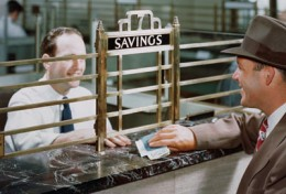 Vintage banking photo. Notice the bars near the teller? Banks today do not have bars for the banking companies feel that bars are too harsh