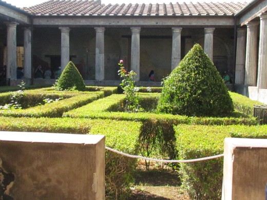 The remains of what was once beautiful courtyards within Pompeii. Today the courtyards are covered by green grass and manicured bushes.