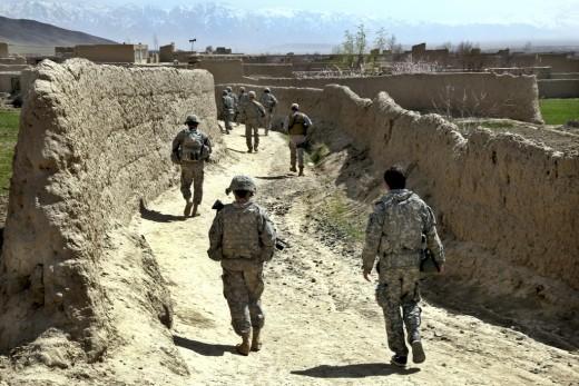 US army soldiers patrol in an Afghani village.