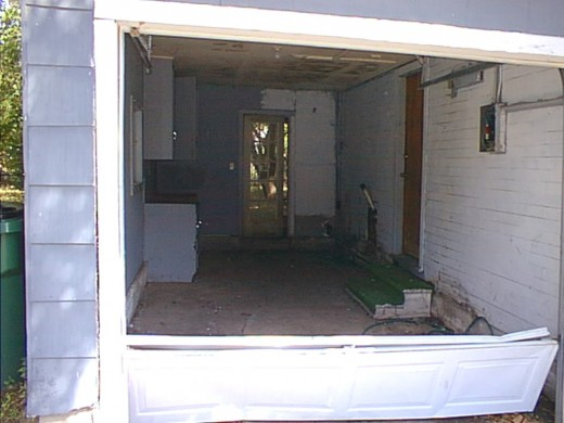 The garage door was damaged beyond repair. The spider-filled interior of the garage led to a side door made of pressed wood.