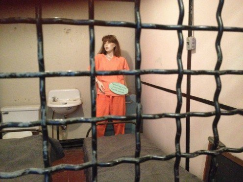 "Photo of a mannequin within ""The Old Jail,"" who is sporting a real prison uniform from the new jail (according to the sign that the mannequin is holding)."