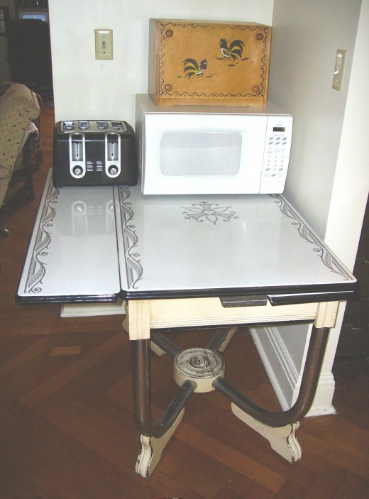 WE USE THIS TABLE TO HOLD OUR MICROWAVE, TOASTER, AND BREADBOX, USING JUST ONE OF THE LEAVES OF THE TABLE...