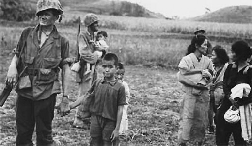 Marines escorting civilians to safety. More than 20,000 non-combatants died during the battle.