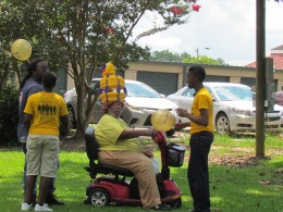 A hat of balloons were displayed on the cookout participant as other young people looked on.
