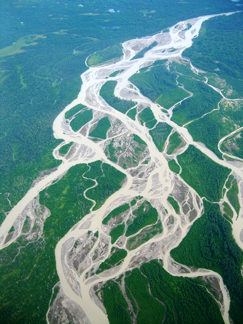 Flowing tributaries meander toward larger bodies of water like lakes and oceans.