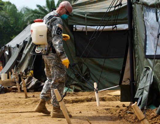 Preventative medicine soldier sprays insecticide around living quarters in Gbediah, Liberia, Dec. 15, 2014. Taken during Operation United Assistance, the joint effort to combat the devastating Ebola outbreak.