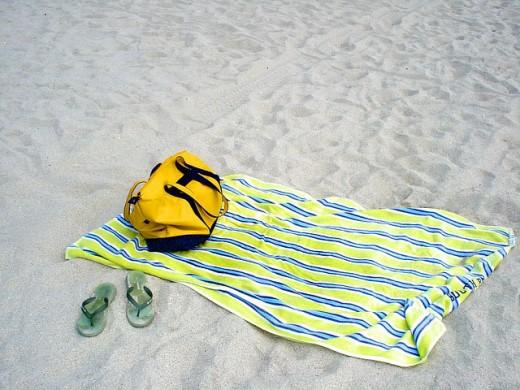 A beach bag, a pair of flip flops, and a beach blanket.