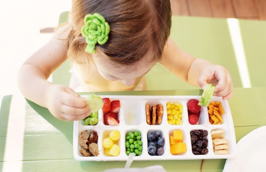 Fill an ice tray with snacks for toddlers or younger children.
