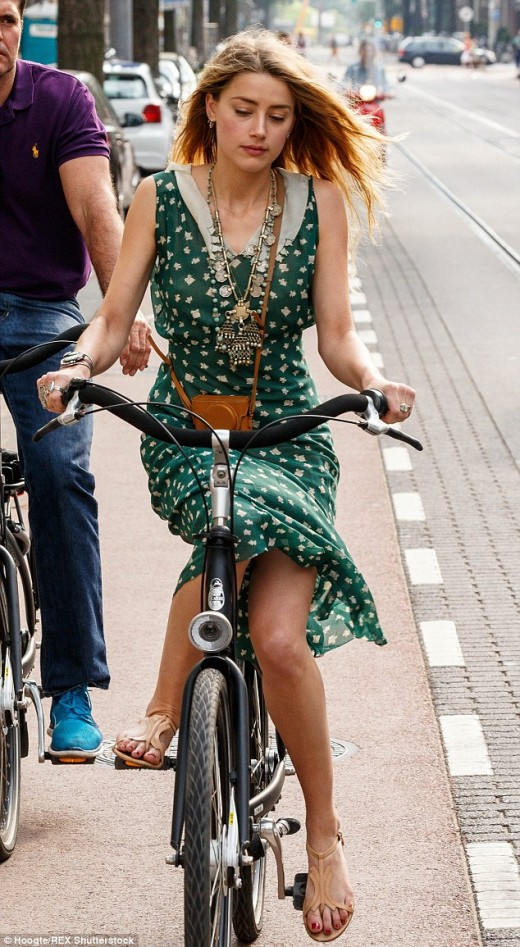 Actress, Amber Heard  rides a bike easy  as drinking water