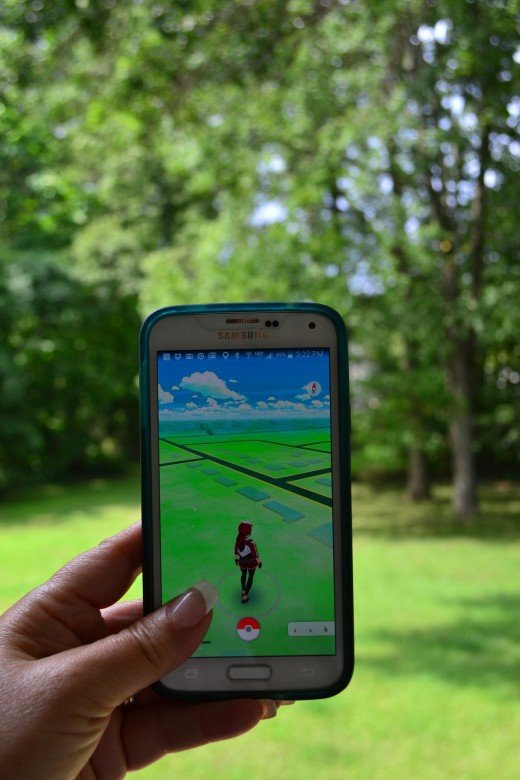 A woman plays Pokemon Go on her cell phone in a city park. Photo by AnaBanana413. CC0 Public Domain.