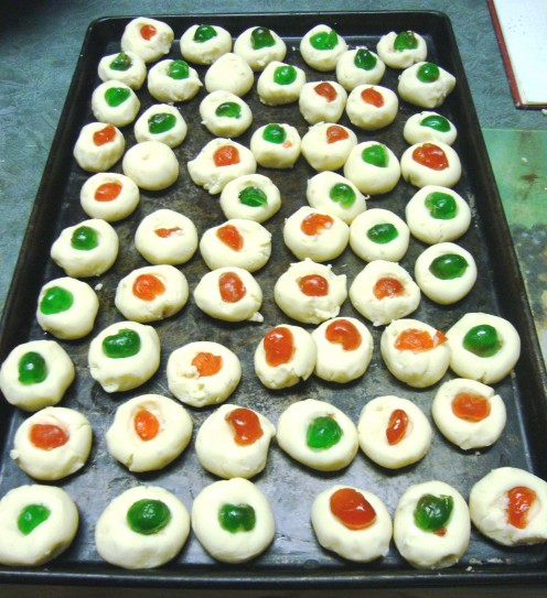 Red and green cherries decorate Xmas shortbread in festive colors.