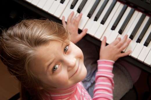 A young girl playing on a keyboard