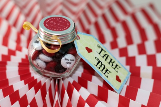 Glass bottles with candy as party favors. In this photo M&Ms were personalized  with the date of the baby shower.