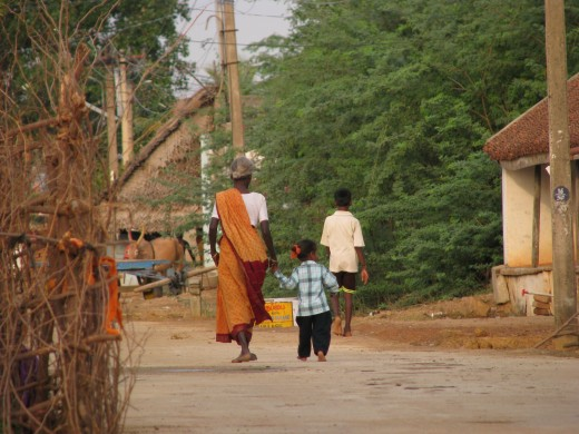 A young girl meanders home at the hand of her grandmother. Although changing in urban areas, in rural India, the traditional multi-generational extended family still predominates.