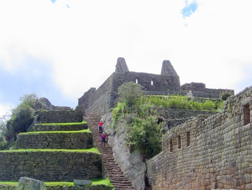 Travelers enjoy coming down the steps from the upper level of Machu Pachu, while viewing the architecture and lush greenery in the ruins.