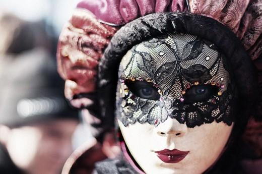 A young girl wearing a venetian mask.