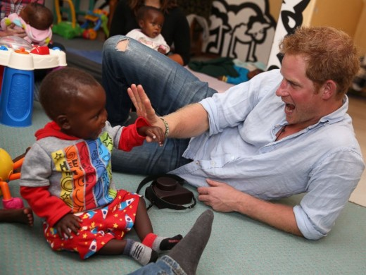 Prince Harry with a child orphaned by AIDS