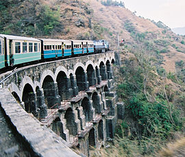 Mountain track train passing over a bridge on the mountains