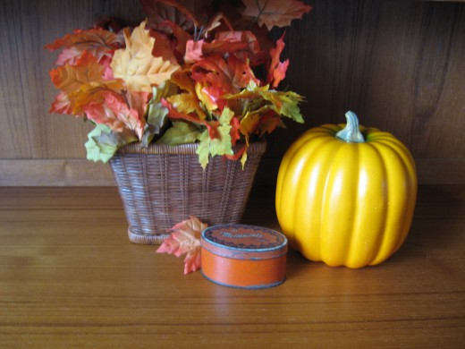 The little tin doesn't have anything to do with autumn, but the color is perfect to combine with this vignette. Groupings like this look more harmonious with an odd number of pieces and different heights to balance it out.