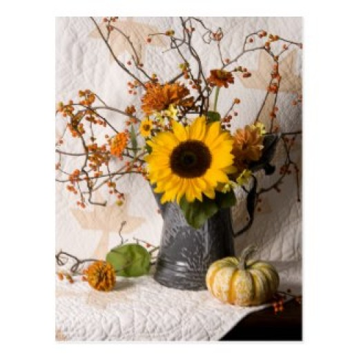 A subtle pattern in the quilt makes a good background for the autumn branches, little pumpkin and the pewter vase. The big sunflower adds a color punch to this mantel display.