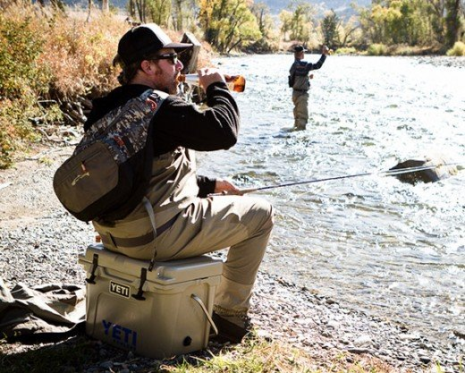 Man sits on a Yeti cooler, pretends to fish.