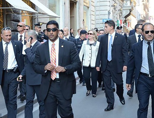Clinton surrounded by an armed security detail