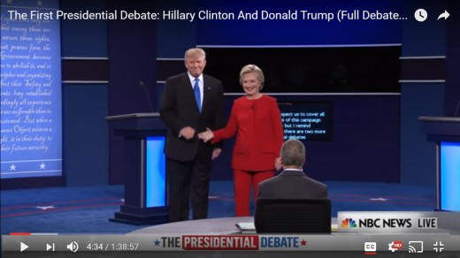 The handshake has ended, and both candidates are square to the audience.  HRC's right arm begins to shift from the handshake toward the audience.