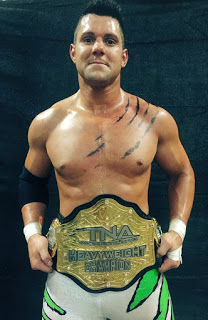 Eddie Edwards holding his TNA World Heavyweight Championship around his waist. The claw mark is just paint used to signify that he is one half of  the 5 time TNA Tag Team Champions,The Wolves
