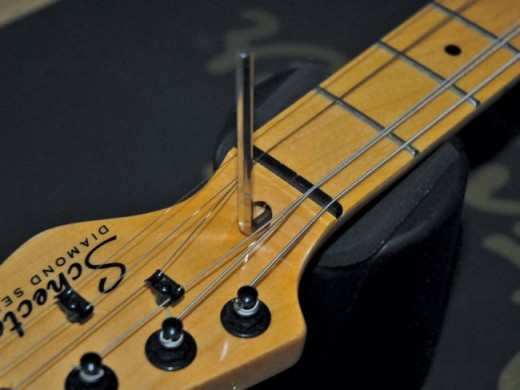 Truss rod adjustment is usually done at the nut end of the neck on electric guitars.