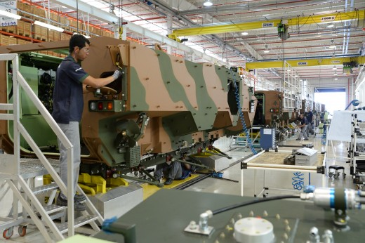Factory workers assemble military vehicles on a production line.