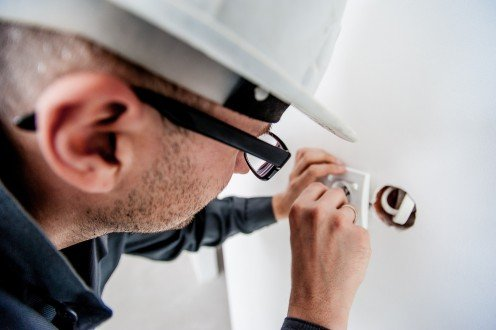 Qualified electrician installing a wall socket.