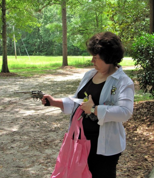 The always-on-the-go Bank of Alapaha Senior Vice President Sylvia Roberts coolly squeezes the trigger of the genuine Smith & Wesson .38 Special revolver used by former Vice President Charlie Matthews to thwart a failed robbery by Jesse James Roberts.
