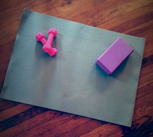 My personal mat, weights, and a yoga block. Inexpensive equipment that you can use to work out at home.