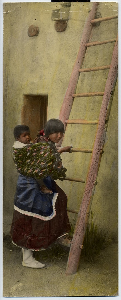Native mother with child climbing ladder at Taos Pueblo