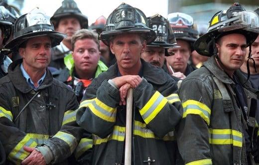 Firefighters look on Friday, Sept. 14, 2001, as President George W. Bush surveys the destruction left by terrorist attacks on New York City on 9-1-1.