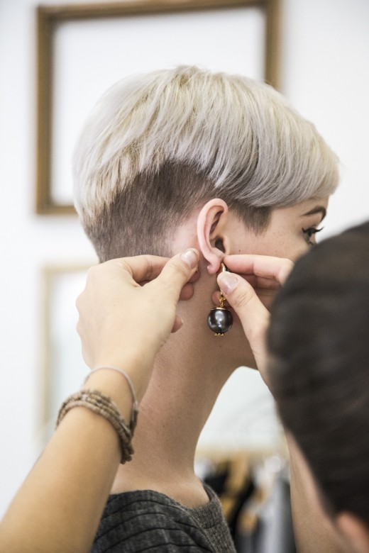 A woman tries on a new earring.