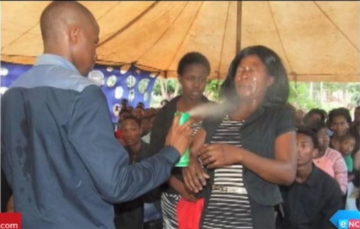 Screengrab/eNCA News: Pastor Lethebo Rabalago of Mount Zion General Assembly spraying Doom pesticide onto a woman's face
